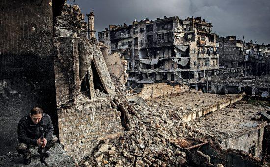אזרח סורי על רקע הריסות העיר חאלב המופגזת