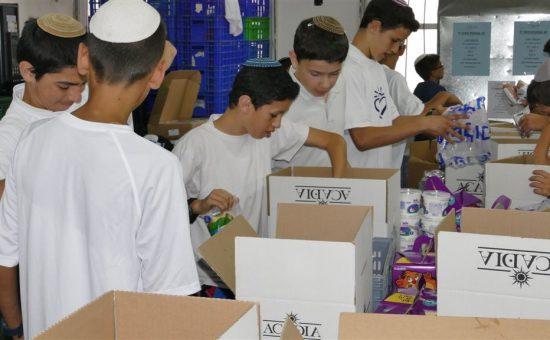 מתנדבי חסדי נעמי אורזים ערכות חג לחלוקה לנזקקים