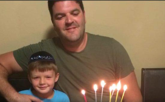 רונן נחמני בהדלקת נרות חנוכה עם אחד מבניו