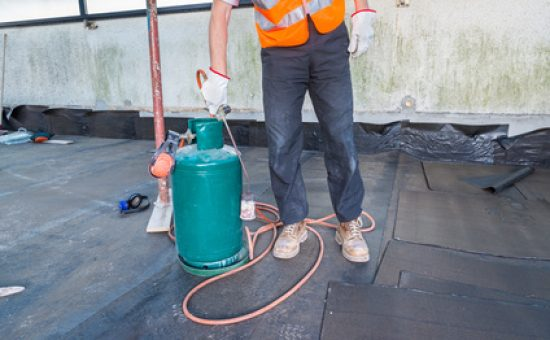 Worker, with a roofing gas torch, is installing rolls of bituminous waterproofing membrane on a terrace - roof of a home
