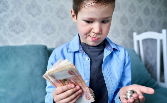 child has ot money one hand small coins other hand doubts